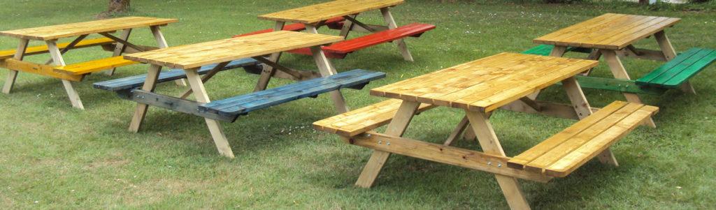 Een set van 5 picknickbanken voor gebruik door de kampeergasten geverfd in verschillende kleuren blauw, groen, rood en geel